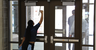 Cleaning front doors of SVES ahead of the start of school